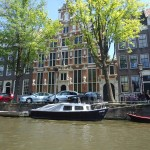 Old Dutch houses and boats along a canal in Amsterdam on Adventures in Expat Land