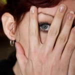Woman Peeking Between Her Hands iStockphoto/asiseeit