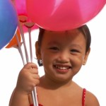 young girl with balloons on www.adventuresinexpatland.com