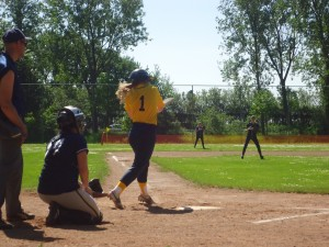Girl batter swinging at the ball in a softball game on www.adventuresinexpatland.com