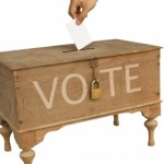 Hand dropping a ballot into a ballot box on www.adventuresinexpatland.com