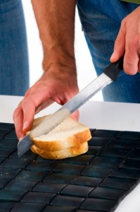 man's hands holding a knife and cutting a sandwich on www.adventuresinexpatland.com